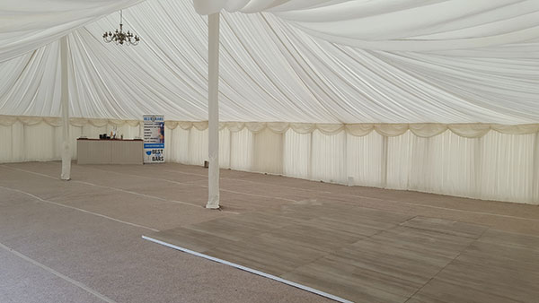 The interior of a solid, semi-permanent marquee for wedding and event hire.