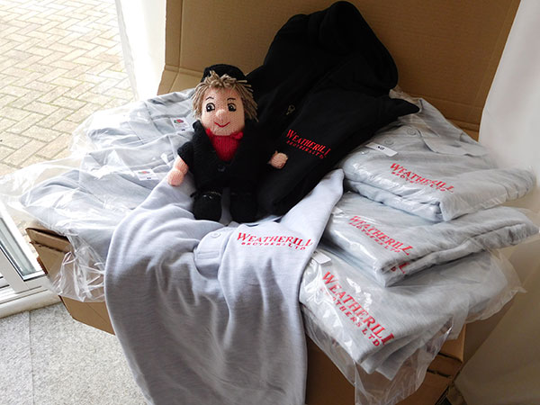 Soft toy sitting on a pile of t-shirts with company embroidery on.